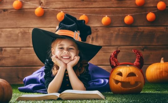 Happy Halloween! Cute cheerful little witch with a book of spell